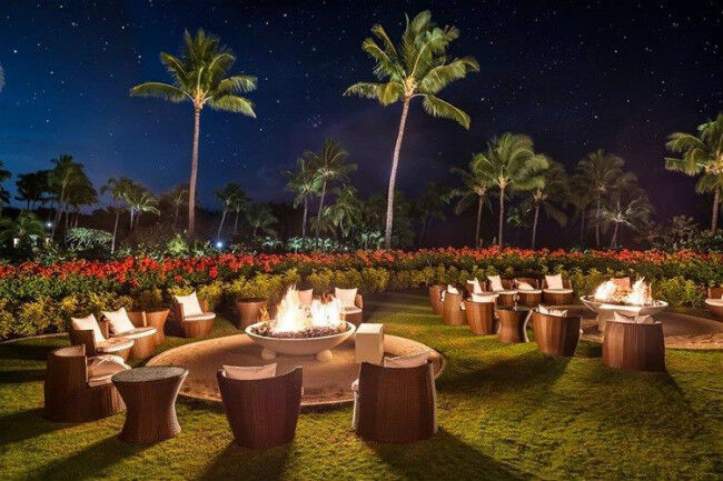 Gas fire pits surrounded by chairs at a Hawaiian resort at night