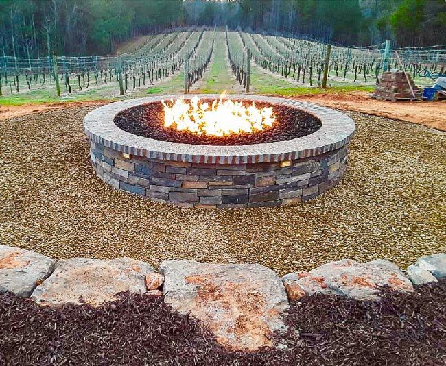 Large masonry fire pit burning in front of a vineyard