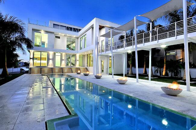 Gas fire bowls along a swimming pool in an ultramodern luxury outdoor patio
