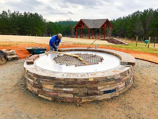 Worker installing a burner into a larege masonry fire pit