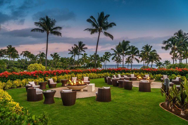 Gas fire pits surrounded by chairs at a Hawaiian resort during sunset