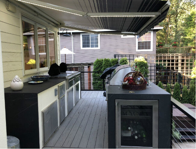 Gray and white outdoor kitchen island with stainless steel components and a built-in grill