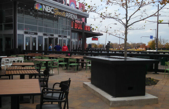 A large black fire pit table on the outdoor patio of the NBC Sports Arena