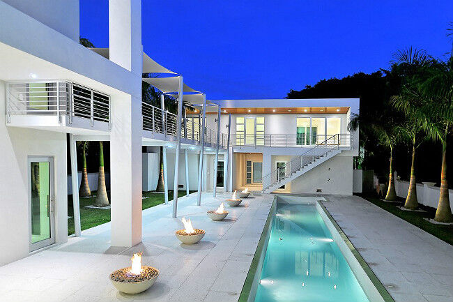 Outdoor patio with a swimming pool and five gas fire bowls at an ultramodern luxury home
