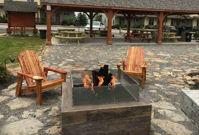Outdoor stone patio with a square fire pit and two adirondack chairs in front of a pavillion