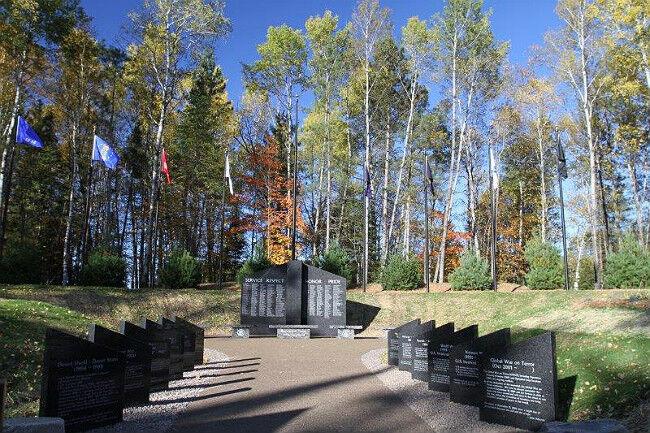 Pathway to gray granite veteran memorial in the woods