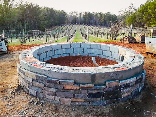 Unfinished masonry fire pit in front of a vineyard