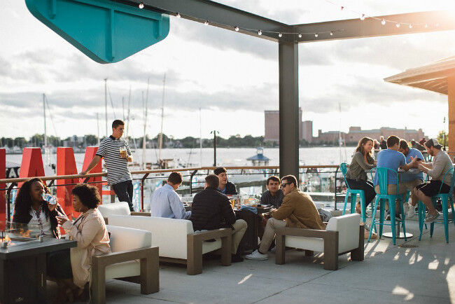 People drinking and dining on an outdoor patio next to the ocean