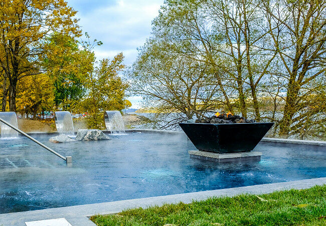 Square black gas fire pit in a vibrant blue pool