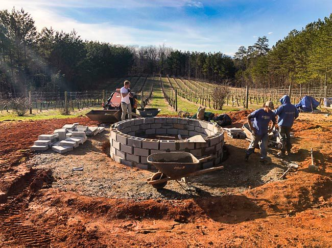 Workers building a fire pit frame in front of a vineyard