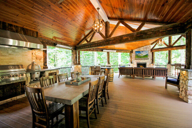 Rustic covered deck with an outdoor kitchen and outdoor living room