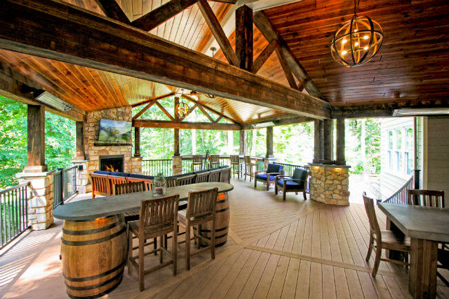 Rustic covered deck with reclaimed wood details and a gas fireplace
