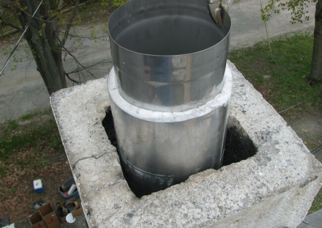 Stainless steel chimney liner sticking out of a masonry chimney