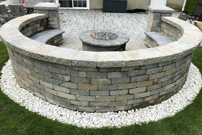 Backview of a masonry fire pit on a stone patio