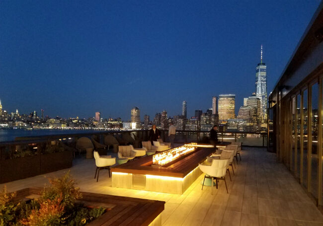 Linear fire pit on a river-front patio overlooking the city